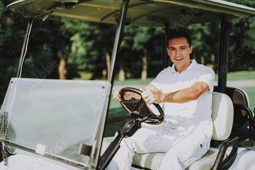 Fotografia  Young Man in White Shirt using Cart on Golf Field.