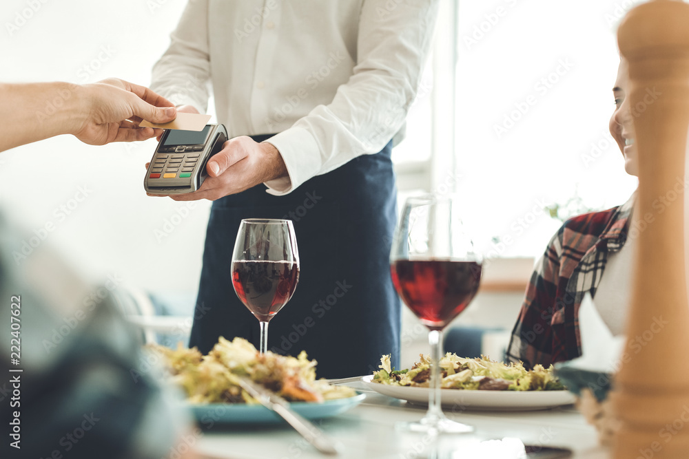 Fototapeta Payment with card. Nice professional waiter holding a money terminal while taking a payment