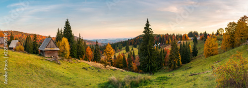 panorama of village in Apuseni mountains. beautiful autumn landscape at sunset. mixed forest in red foliage. wonderful rural countryside of Romania