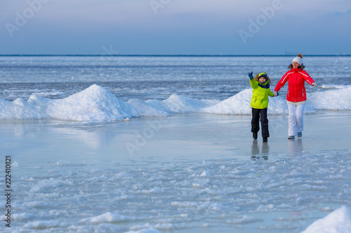 Fotografie, Obraz  Young mother and her son on icy beach