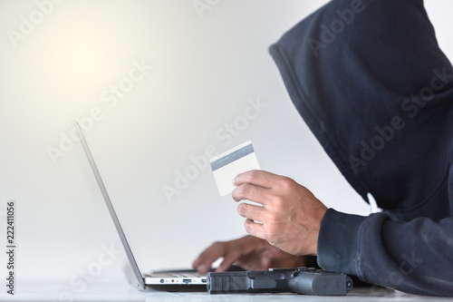 Hacker working on a code and stealing credit card, man wearing a balaclava and holding a credit card behind a laptop.