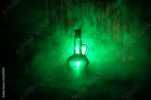 Fotografía Antique and vintage glass bottles on dark foggy background with light