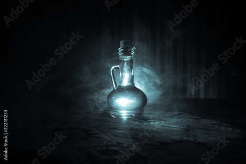 Photo  Antique and vintage glass bottles on dark foggy background with light
