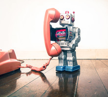 Big Silver Robot Toy On  A  Retyro  Phone Standing On An Old Wooden