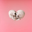 canvas print picture - Two skulls in heart shape kissing on pastel pink background. Minimal love concept.