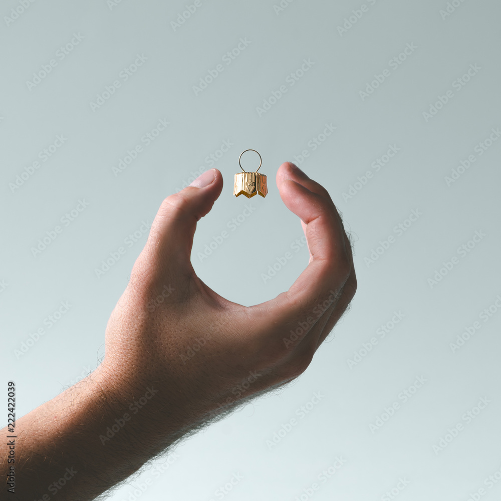 Fototapety, obrazy: Hand holding Christmas bauble decoration. Minimal New Year concept art.