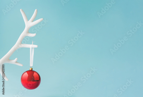 White reindeer antler with red Christmas bauble decoration on pastel blue background. New Year minimal concept.