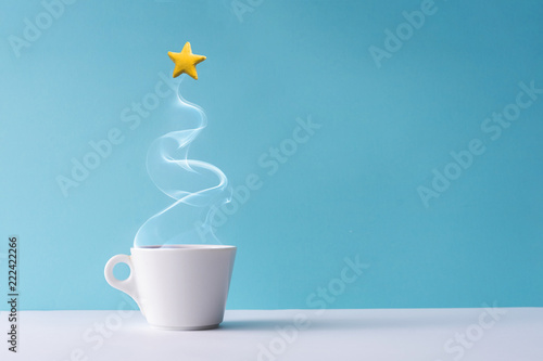Recess Fitting Tea Christmas tree made of steaming coffee or hot drink with yellow star cookie. Winter holiday concept. Minimal New Year background.