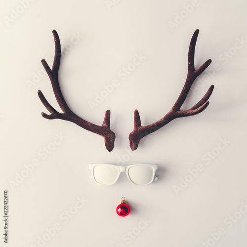 Santas reindeer made of antlers, white sunglasses and red New Year bauble decoration. Minimal winter holiday concept.