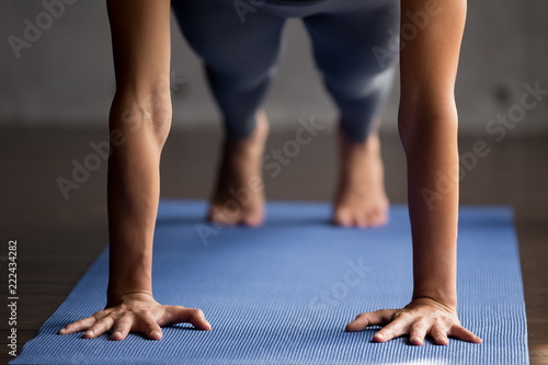 Photo  Sporty slim woman practicing yoga, doing Push ups or press ups exercise, Plank pose, working out wearing sportswear pants, hands close up view, indoor yoga studio