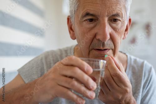 Foto Senior man taking medicine