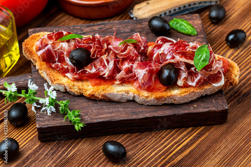 Foto  Delicious bread toast with natural tomato, extra virgin olive oil, Iberian ham, black olives and basil leaves