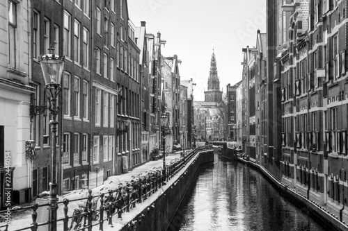 Beautiful view of the famous Oudezijds Kolk in Amsterdam, the Netherlands, in black and white. In the background is the Oude Kerk (Old Church, 1213) in the Red Light District