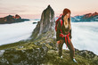 Woman with backpack hiking in sunset  mountains adventure outdoor in Norway active vacations traveling lifestyle Segla peak
