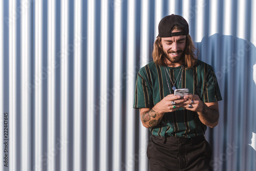 Front view of young man with beard long hair and cap using his mobile phone in the city on a sunny day of summer