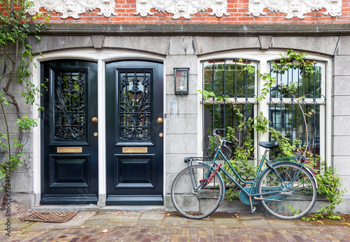Photo  Typical house entrance with two doors, window, and bicycle in the old town of Am