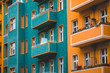Leinwanddruck Bild - green and orange colored facade in detail view with small balcony