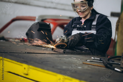 Fotografia, Obraz Strong and worthy woman doing hard job in car and motorcycle repair shop