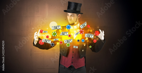 фотография  Young illusionist in tails hold between hands gambling staffs with super power