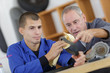 Workers looking at mechanical parts on work bench