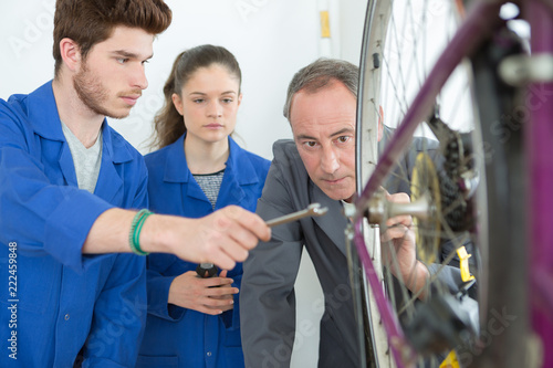 Fototapety, obrazy: manager checking bicycle next to apprentices