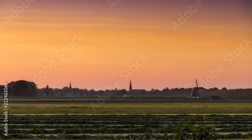 Skyline of Abcoude, the Netherlands, at sunset in spring, view over the rural pastures from Baambrugge with a windmill and churches