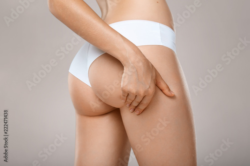 Unrecognizable woman in underwear testing fat layer on hips Canvas-taulu