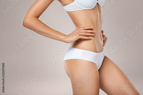 Obraz Unrecognizable slim tanned woman body in underwear - fototapety do salonu