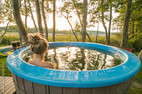 Leinwand Poster Woman enjoys outdoor hot tub in nature