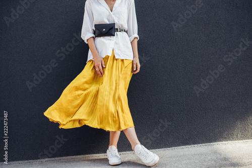 Valokuva Horizontal cropped body image of beautiful slim woman in beautiful yellow skirt