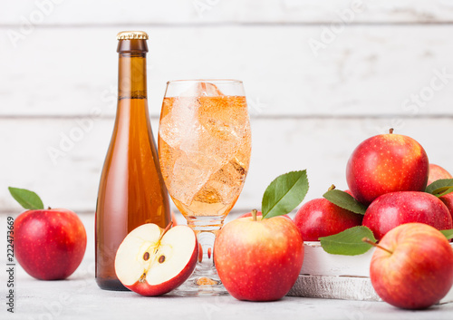 Fotografia Bottle and glass of homemade organic apple cider with fresh apples in box on woo
