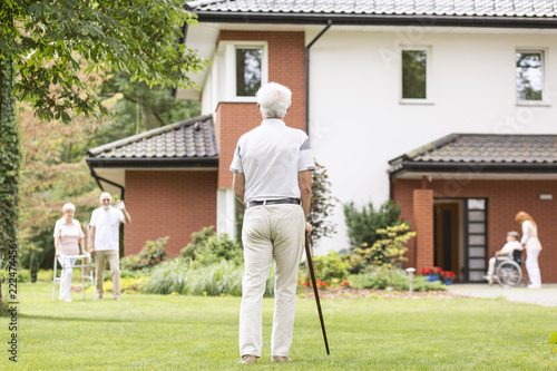 Obraz A back of a gray-haired senior man with a cane looking at his fellow mates outside of a luxury nursing home. - fototapety do salonu