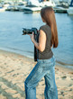 on the beach girl in jeans rear view, holding a camera