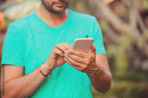 Fotografiet  Modern man using cellphone outdoors.