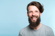 Leinwanddruck Bild emotion expression. very happy joyful thrilled to bits man with beaming smile. young handsome bearded guy portrait on blue background.