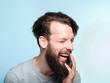 Leinwanddruck Bild happiness enjoyment and laugh. man with a wide grin. portrait of a young bearded guy on blue background. emotion facial expression. feelings and people reaction.