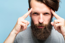 Mind Games And Brain Power. Mentalist And Cognitive Skills Concept. Man Concentrating And Holding Index Fingers On Temples. Young Bearded Guy Portrait On Blue Background.