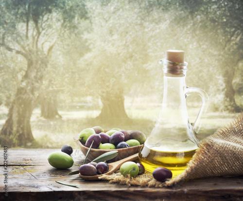 Obraz na płótnie Olives and bottle of olive oil on wooden table in olive garden