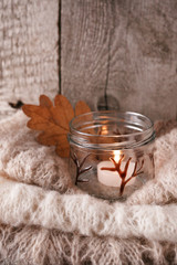 Obraz na płótnie Canvas Details of still life in the home interior living room. Beautiful candlestick, warm cloth, candle on wooden background. Vintage, rustic. Cozy autumn fall winter concept