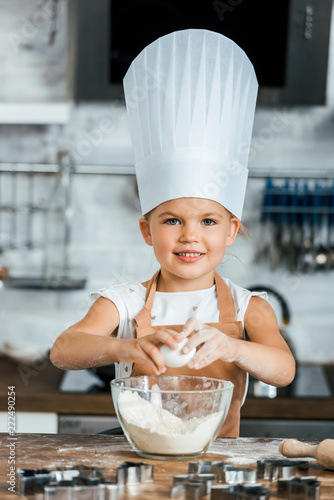 adorable child in aron and chef hat cooking dough and smiling at camera Canvas Print