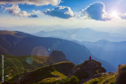 Foto op Canvas Zwart person in the beautiful mountain landscape of Ceahlau, Romania. Lens flare added in the photo
