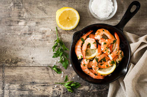Grilled shrimps, parsley and lemon in iron pan on wooden table. Top view. Copyspace