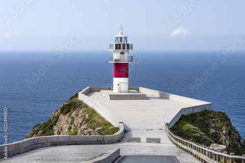 Montage in der Fensternische Leuchtturm Beautiful red white striped lighthouse with seascape, road, coastline, ocean sea water, cliff, skyline and blue sky in the background concept nautical maritime danger navigation hazard travel traffic