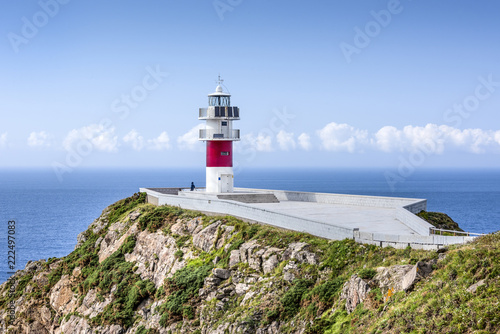 Foto op Aluminium Vuurtoren Spain, Cabo Ortegal: Seascape with beautiful red white striped lighthouse, people tourists, coastline, ocean sea water, cliff, skyline and blue sky in background - concept navigation. July 13, 2018