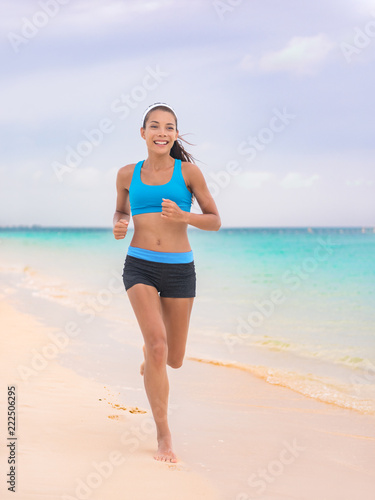 Spoed Foto op Canvas womenART Active lifestyle young woman jogging on beach. Running barefoot on sand in Hawaii vacation travel Asian girl running on tropical holiday in blue activewear outfit.