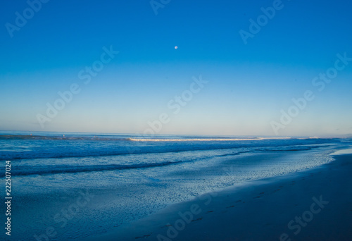 Staande foto Zee / Oceaan Ashtonishing view of waves, sand beach in a gorgeous sunny day on Santa Teresa beach with a moon in the blue sky