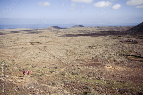 Couple hiking in volcanic landscape descending Calderon Hondo, Fuerteventura, Canary Islands, Spain