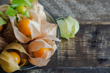 Physalis In Bowl On Dark Wooden Background.