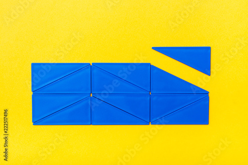 Fotografie, Obraz  Blue plastic triangles are laid out in straight rows in a rectangle on a yellow background