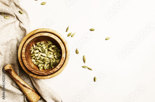 Fototapeta Dried cardamom in wooden bowl with pestle, white background, top view obraz